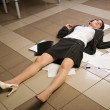 Lifeless businesswoman in a office - Stock Photo