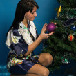 Pretty woman decorate a Christmas tree — ストック写真