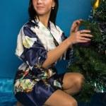 Pretty woman decorate a Christmas tree — Stock Photo