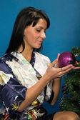 Pretty woman decorate a Christmas tree — Stockfoto