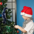 Boy wearing santa claus clothes with a new year gift — Stock Photo