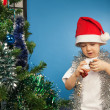 Stock Photo: Boy wearing santa claus clothes with a new year gift