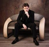 Muž v černém obleku, sedí na pohovce — Stock fotografie