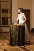 若い女性は豊かなインテリアでチェスをプレイします。 — ストック写真