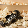 Stock Photo: Black metal planer on wooden plank