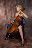 Woman in evening dress playing cello — Stock Photo