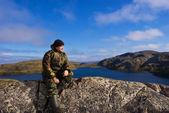 Uomo si siede sulla cima di una montagna. cresta musta tunturi. — Foto Stock