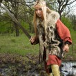 Stock Photo: Viking girl with sword in a wood