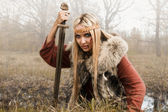 Viking girl with sword in a fog — Stock Photo