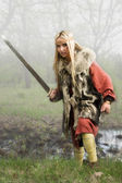 Viking girl with sword in a fog wood — Stock Photo