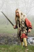 Viking girl med svärd i en dimma trä — Stockfoto