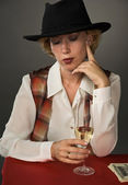 Beautiful woman in a black hat with a wine glass — Stock Photo