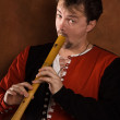 Man in a medieval suit plays a flute — Stock Photo