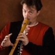Man in a medieval suit plays a flute — Stock Photo #9440417