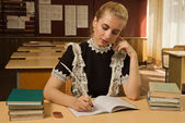 Confident school girl at her desk — Stock Photo