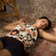 Brunette asleep on a floor - Stock Photo