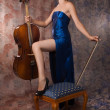 Woman in evening dress posing with cello - Stock Photo