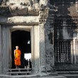 Постер, плакат: Buddhist monk posing for photographers in Angkor Wat temple
