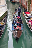 Gondoliero sailing with tourists on gondola in Venice channel, J — Stock Photo
