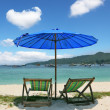 A chaise lounges and dark blue beach umbrella — Stock Photo