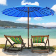 Royalty-Free Stock Photo: A blue beach umbrella and striped chaise lounges