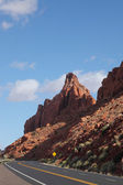 The road passes between red sandstone — Stock Photo