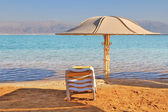 The beach umbrella and a chaise lounge expect tourists — Stock Photo