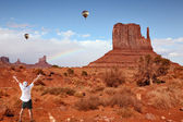 Enthusiastic tourists in Monument Valley and colorful balloons — Stock Photo