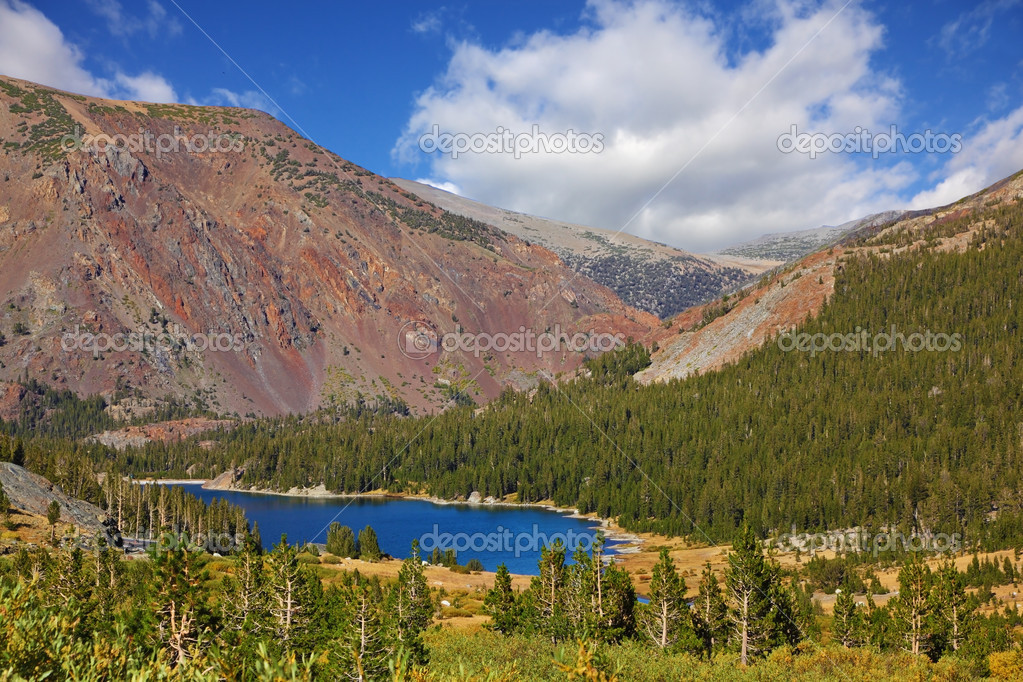 Picturesque huge red mountain on coast of dark blue lake Tioga in park Yosemite, the USA  Stock Photo #9948713