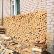 Stock Photo: Firewood near wall of the rural building