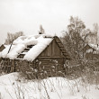 Old wooden house amongst winter snow — Stock Photo