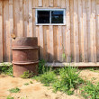 Rusty barrel near wooden shed — Stock Photo