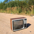 Old television set on rural road — Stock Photo