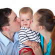 Stock Photo: Happy parents kiss babe.