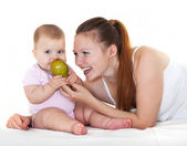 Happy mum feeds with a pear the babe. — Stock Photo