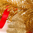 Golden christmas tree toy on golden fir-tree branch — Stock Photo