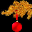 Red Christmas ball on a ribbon against black background — Stock Photo