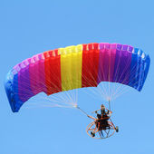 Colorful paraglider on blue bright sky — Stock Photo