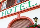 Close-up of an old hotel wall with windows and a sign — Stock Photo