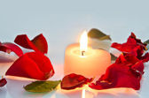 A burning candle in the shape of a heart in rose petals — Stock Photo