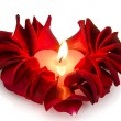 Royalty-Free Stock Photo: A burning candle in rose petals in heart shape