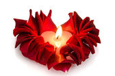 A burning candle in rose petals in heart shape — Stock Photo