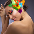 Beautiful young female face with bright fashion multicolored make-up & — Stock fotografie