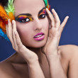 Beautiful young female face with bright fashion multicolored make-up & — Stockfoto