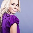 Fashionable blond girl smiling on violet dress. — Stock Photo #8974979