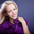 Fashionable blond girl smiling on violet dress. — Stock Photo