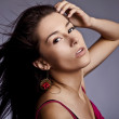 Young beautiful brunette pose in a fashionable dress. Studio photo. — Stock Photo