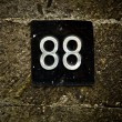 Numbers 88 on old stone wall. - 图库照片