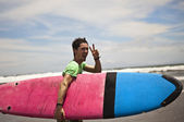 Young attractive surfer with a surf board — Стоковое фото