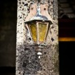 An old street lamp is hanging on wall - Stock Photo